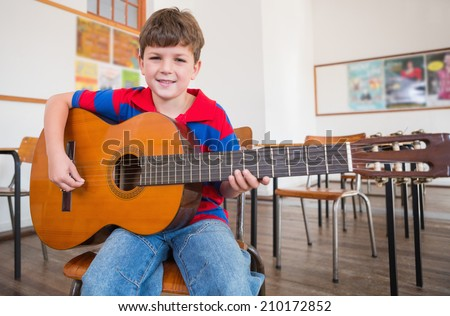 Cute pupil playing guitar in classroom at the elementary school - stock photo