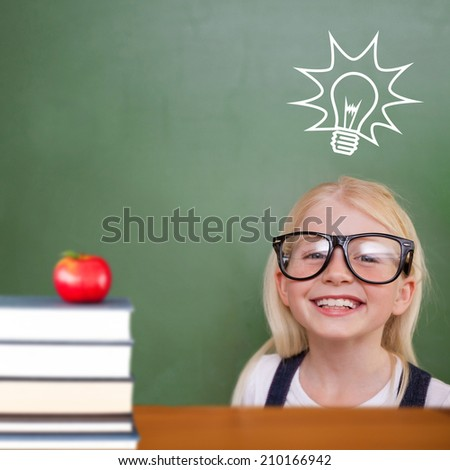 Cute pupil smiling against red apple on pile of books - stock photo
