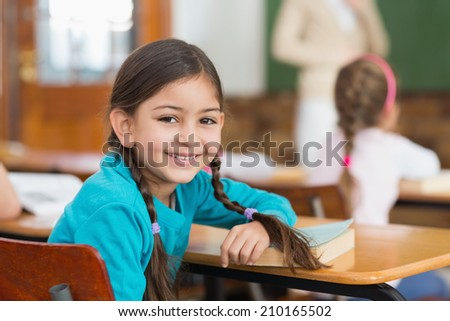 Cute pupil smiling at camera at her desk in classroom at the elementary school - stock photo