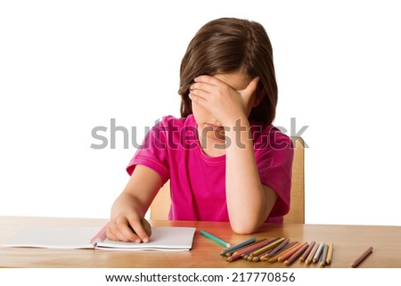 Cute pupil working at her desk on white background - stock photo