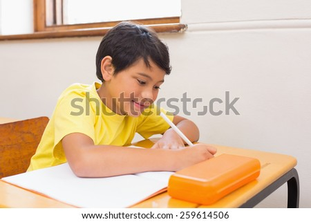 Cute pupil writing at desk in classroom at the elementary school - stock photo
