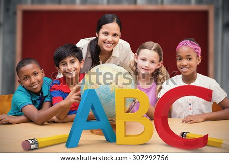 Cute pupils and teacher looking at globe in library against blackboard with copy space on wooden board - stock photo