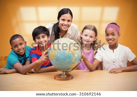 Cute pupils and teacher looking at globe in library against room with large window showing city - stock photo