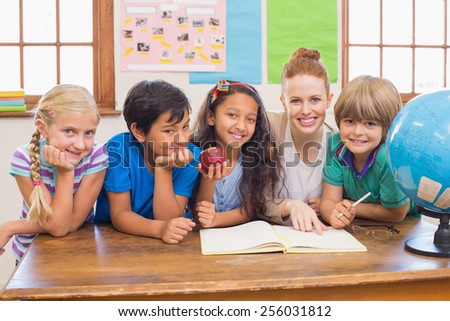 Cute pupils and teacher smiling at camera in classroom at the elementary school