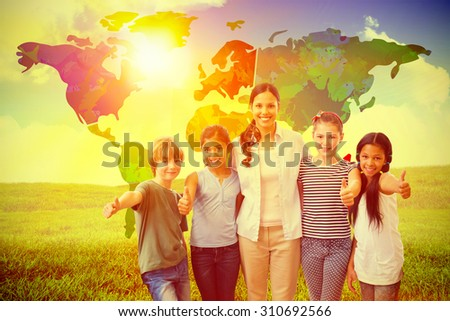 Cute pupils and teacher smiling at camera in computer class against green field under blue sky - stock photo