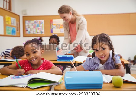 Cute pupils drawing at desk in classroom at the elementary school - stock photo