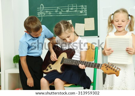 Cute pupils having music lesson in classroom at elementary school - stock photo