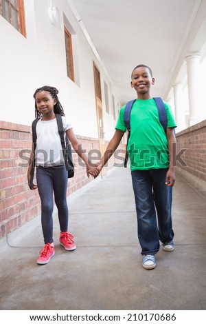 Cute pupils holding hands in corridor at the elementary school - stock photo