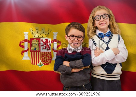 Cute pupils looking at camera against digitally generated spanish national flag - stock photo