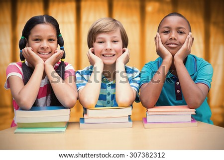Cute pupils looking at camera in library against window overlooking city - stock photo