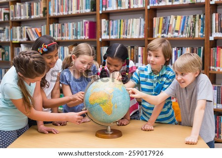 Cute pupils looking at globe in library at the elementary school - stock photo