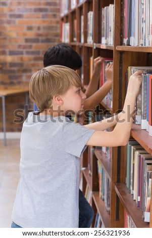 Cute pupils looking for books in library at the elementary school - stock photo