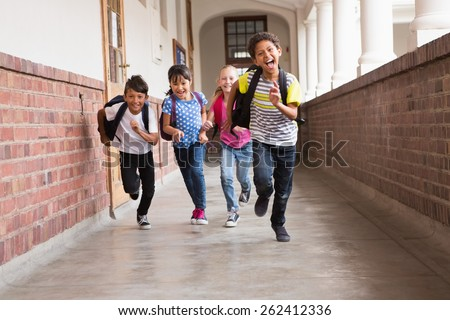 Cute pupils running down the hall at the elementary school - stock photo