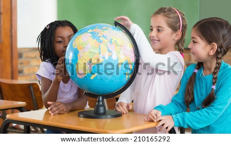 Cute pupils sitting in classroom with globe at the elementary school - stock photo
