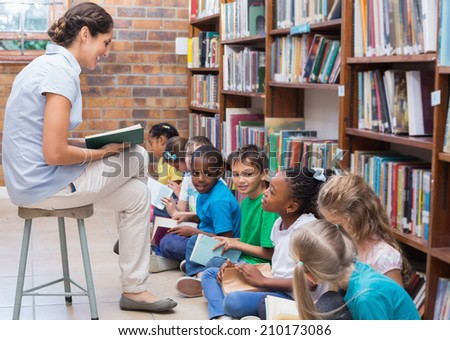 Cute pupils sitting on floor in library at the elementary school - stock photo