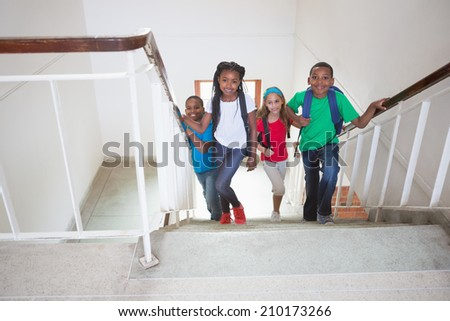 Cute pupils smiling and walking up stairs at the elementary school