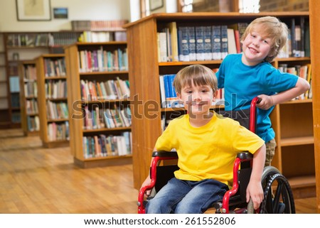 Cute pupils smiling at camera at the library at elementary school - stock photo