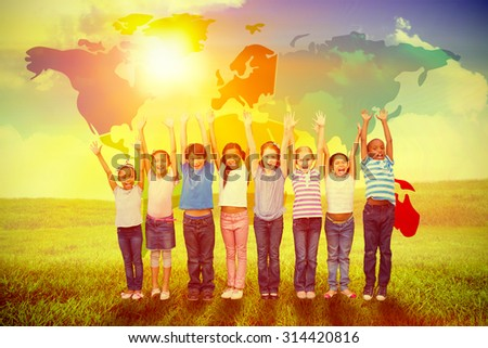 Cute pupils smiling at camera in classroom against green field under blue sky - stock photo