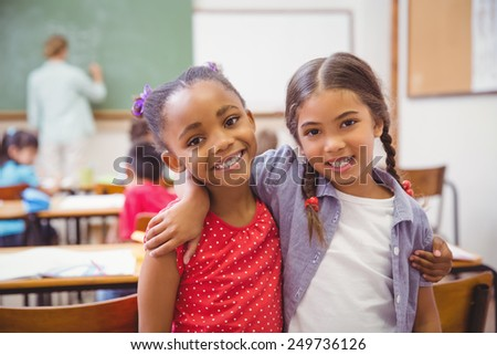 Cute pupils smiling at camera in classroom in slow motion - stock photo