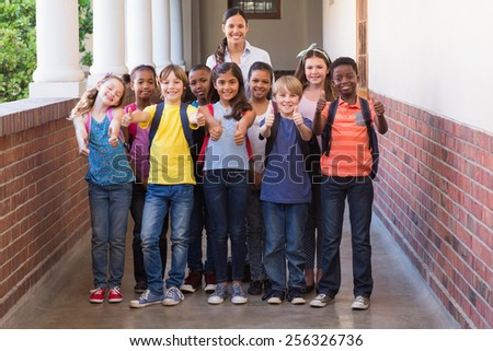 Cute pupils smiling at camera in the hall at the elementary school - stock photo