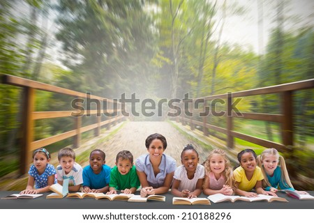Cute pupils smiling at camera with teacher against bridge with railings leading towards forest - stock photo
