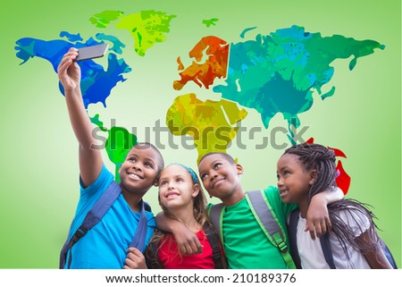 Cute pupils taking a selfie against green vignette with world map - stock photo