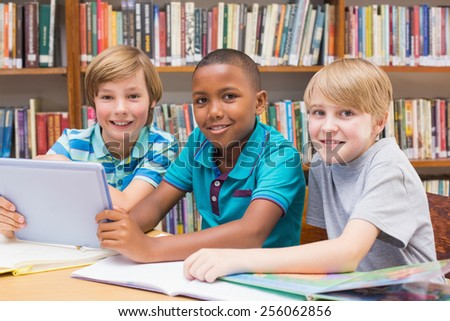 Cute pupils using tablet computer in library at the elementary school - stock photo