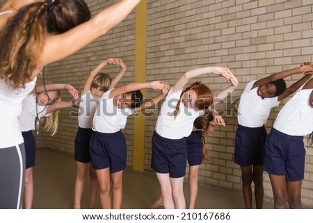 Cute pupils warming up in PE uniform at the elementary school - stock photo