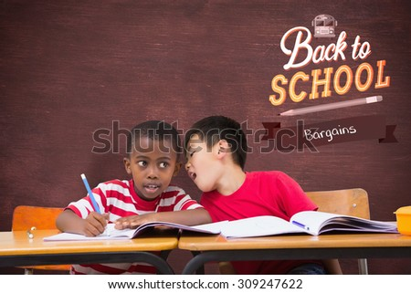 Cute pupils writing at desk in classroom against desk