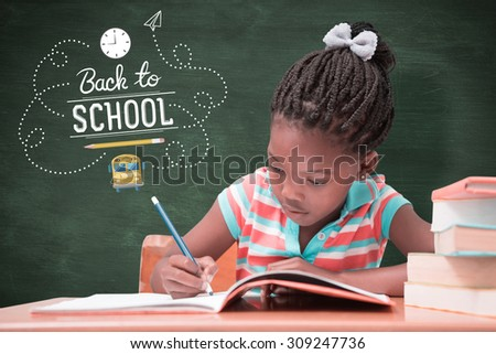 Cute pupils writing at desk in classroom against green chalkboard - stock photo