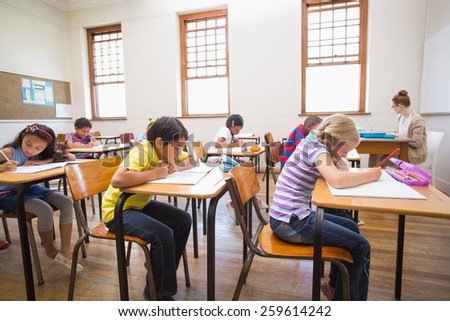 Cute pupils writing at desk in classroom at the elementary school - stock photo