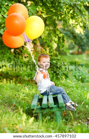 cute red-haired boy with his mother and an armful of balloons - stock photo