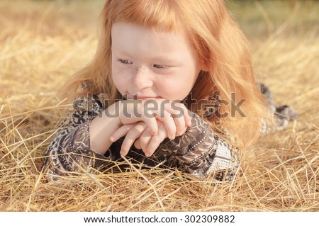 cute red-haired girl with a funny cut bangs hugging lying in the straw - stock photo