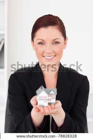 Cute red-haired woman in suit holding a miniature house while sitting in an office