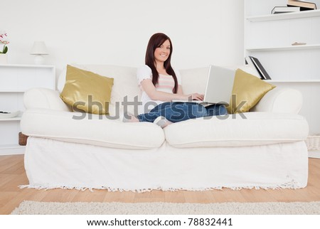 Cute red-haired woman relaxing with her laptop while sitting on a sofa in the living room