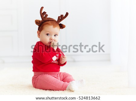 cute redhead baby eating christmas candy at home