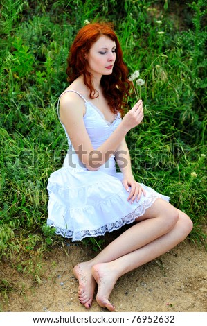 Cute redhead girl who was blowing on a dandelions in her hands. - stock photo