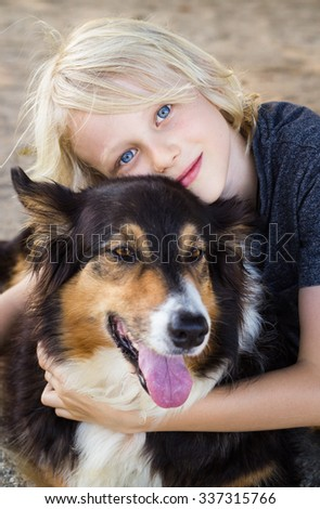Cute, relaxed child  hugging his pet dog - stock photo