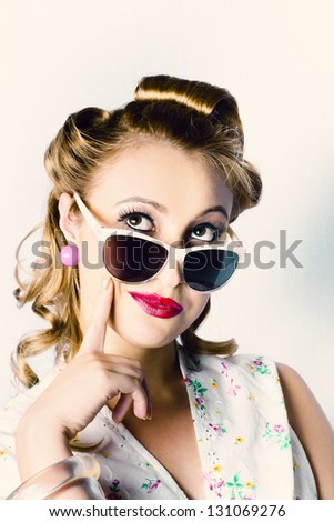 Cute Retro Woman With French Hair Rolls And Bright Make Up Thinking With Finger To Face In Retro Sunshades - stock photo