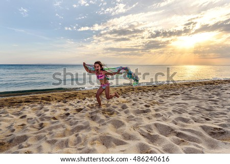 Cute Running Little Girl on Sunset Beach