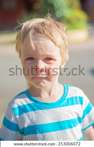 Cute sad little boy in striped t-shirt - stock photo