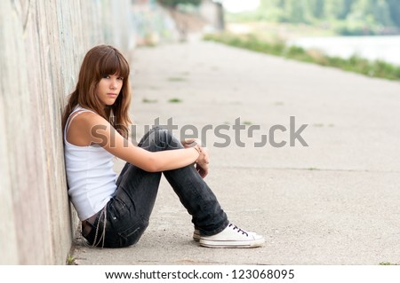Cute sad teenage girl sitting alone in urban environment.