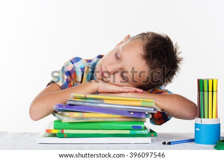 Cute school boy is dreaming on books - stock photo