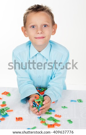 Cute school boy is playing with plastic letters - stock photo