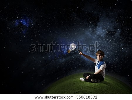 Cute school boy sitting on grass and touching glass light bulb with finger - stock photo