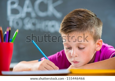 Cute school boy studying in classroom foreground blackboard - stock photo