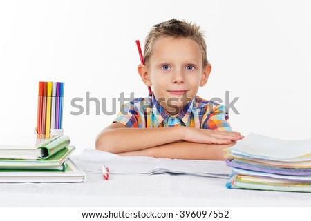 Cute school boy with pencil behind his ear - stock photo