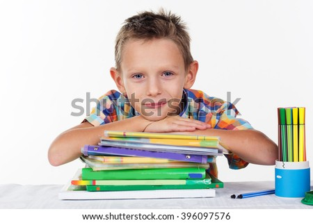 Cute school boy with pile of colorful books - stock photo
