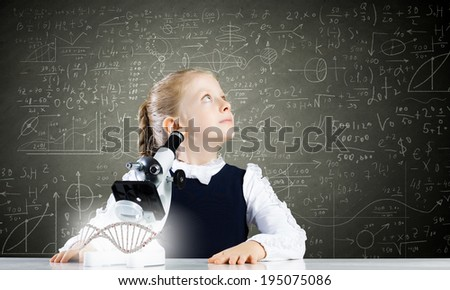 Cute school girl examining dna molecule with microscope - stock photo