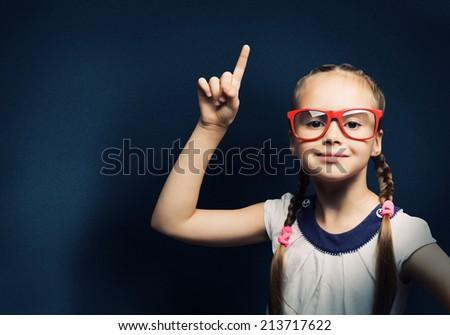 Cute school girl in glasses standing at blackboard - stock photo